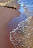 Tranquil waves running over red sand coast. poster