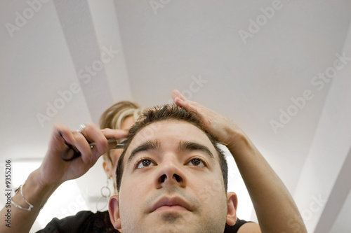 A young man getting his hair cut by a hairdresser at a salon