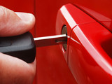 Extreme close-up of man inserting key into car lock poster