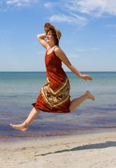 Girl in hat running along snad sea beach