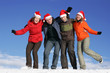Friends with Santa hats have fun on flank of hill