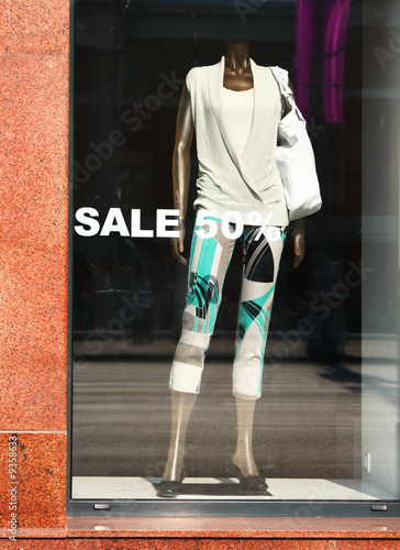 "Shop window with word ""sale"" and mannequin inside"