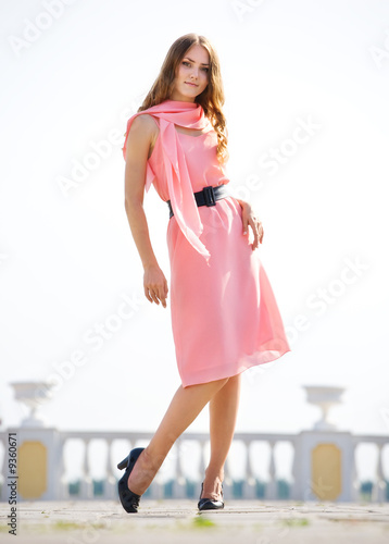 Young slim woman in pink dress.