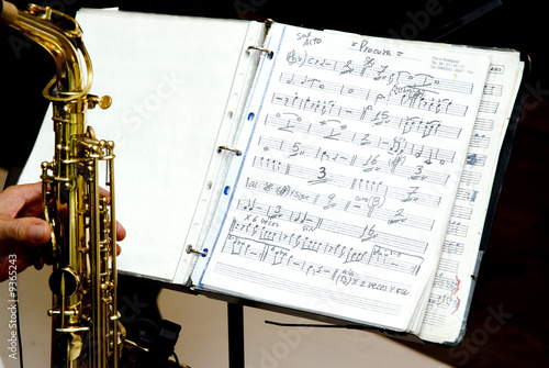 A music score and a musician whit saxophone