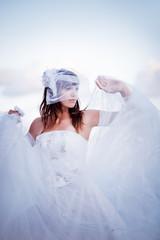 Fashion bride in fluffy wedding dress posing outdoors