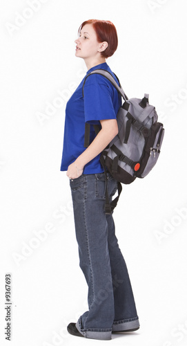Young redheaded girl with a backpack standing up