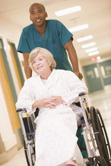 An Orderly Pushing A Senior Woman In A Wheelchair
