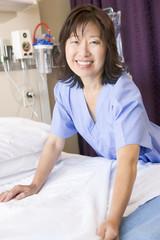 A Nurse Making A Bed In A Hospital Ward