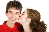 Teen boy getting a kiss on the cheek from his girlfriend. poster
