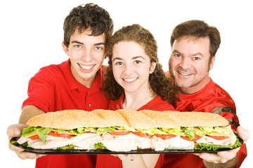 Football fans holding a giant submarine sandwich.  Isolated