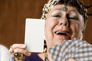 Gypsy fortune teller holding a blank tarot card