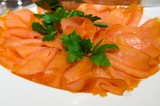 An image of decadent thinly sliced smoked salmon with garnish poster