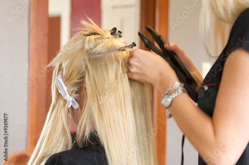 Image of a hairdresser applying extensions to a client's hair