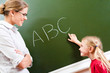 Image of smart girl pointing at letter on blackboard