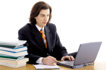 long haired man in suit on white with laptop and books