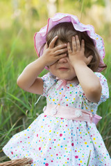 Little girl in pink hat playing peek-a-boo