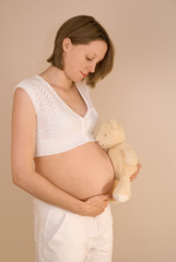 Pregnant woman holds a teddy bear whilst caressing her tummy
