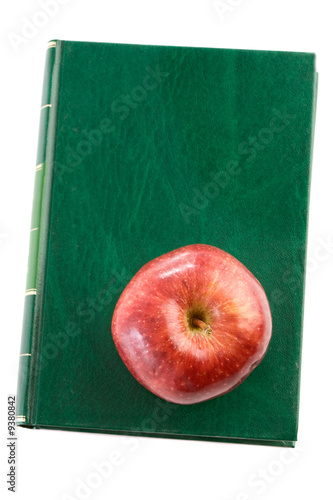 Apple red on a green book seen from above isolated