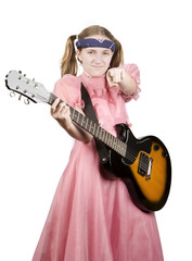 Young girl in a pink dress with an electric rock guitar pointing