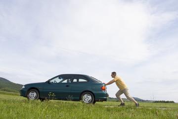 Mann schiebt sein Auto mit leerem Tank