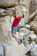 Rock climber clinging to an overhang.