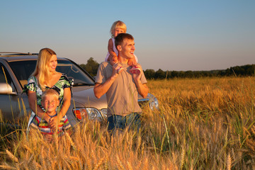Family with offroad car on wheaten field