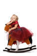Portrait of the beautiful girl on a toy horse;