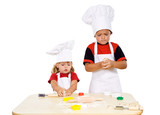 Two kids preparing the cookies from the dough - isolated poster