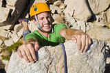 A rock climber desperately clinging to a cliff. poster