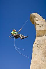 A rock climber rappelling.