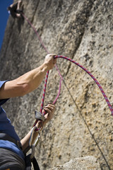 Rock climber being lowered by his partner .