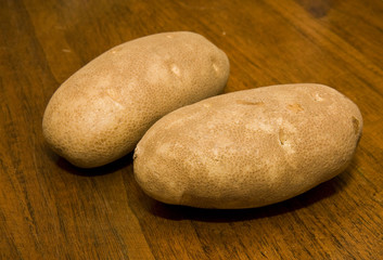 Two potatoes on a wood table