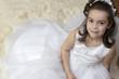 Leinwanddruck Bild - Portrait of a little girl in communion dress and veil.