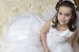 Portrait of a little girl in communion dress and veil.