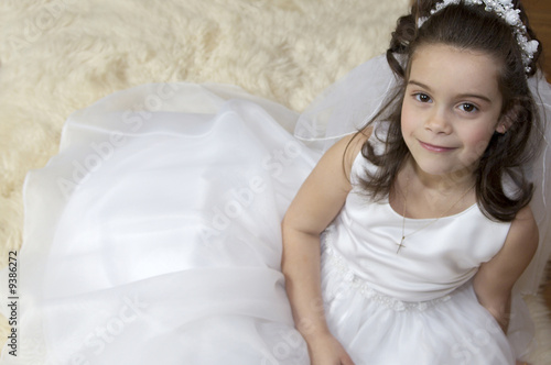 Leinwanddruck Bild Portrait of a little girl in communion dress and veil.