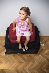 Happy little girl sitting on top of a pile of suitcases