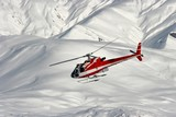 Mountain rescue helicopter on a snowy landscape poster