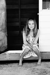 Girl sitting in a doorway smiling