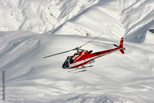 Mountain rescue helicopter on a snowy landscape - 9389652