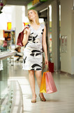 The young beautiful woman with purchases with shop poster