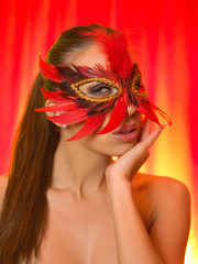 attractive beautiful young woman wearing red carnival mask