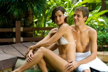 A young attractive couple lying by a jacuzzi in tropical setting