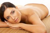 Fototapety Beautiful brunette woman laying on bamboo mat