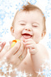 laughing baby boy in mother hands playing with rubber duck