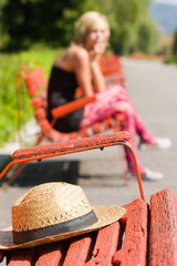 Woman in blurred background, with a hat left alone on the bench
