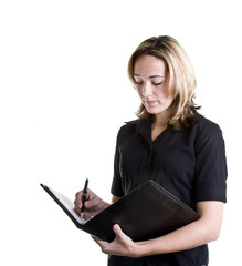A blonde woman in a black shirt writing in a notebook
