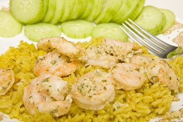 A plate of spicy shrimp over rice with sliced cucumbers
