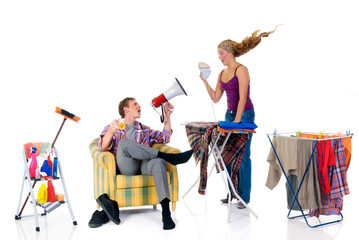 Young bossy man with megaphone,  woman ironing clothing