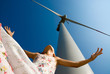 low view of girl in the wind under a turbine