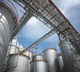 chemical plant and storage tanks, sunny day poster